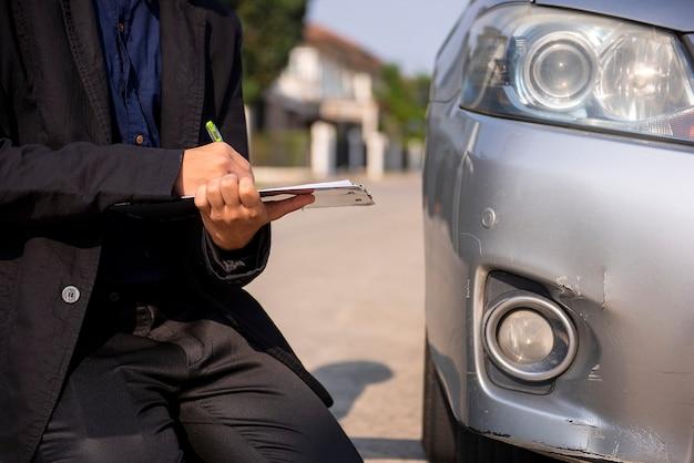 Oficiais da companhia de seguros verificam os estragos do carro dos acidentes de trânsito