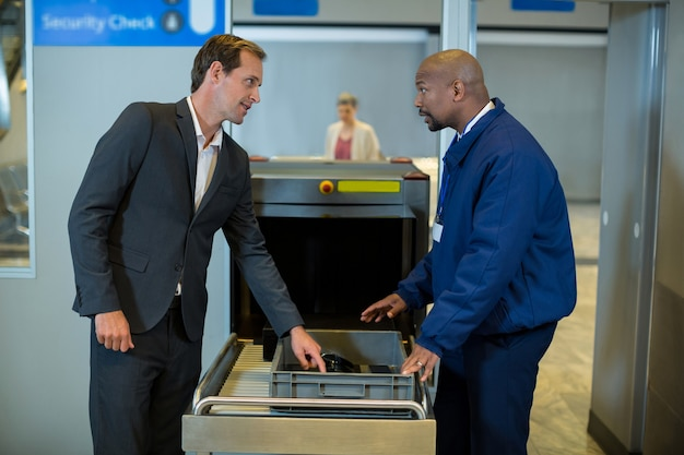 Oficial de segurança do aeroporto interagindo com o passageiro ao verificar um pacote