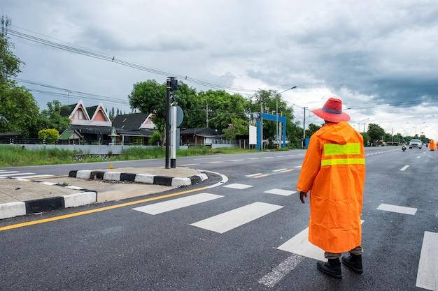 Oficial de trânsito vestindo o custo de chuva laranja com controle e direcionamento do tráfego no interior