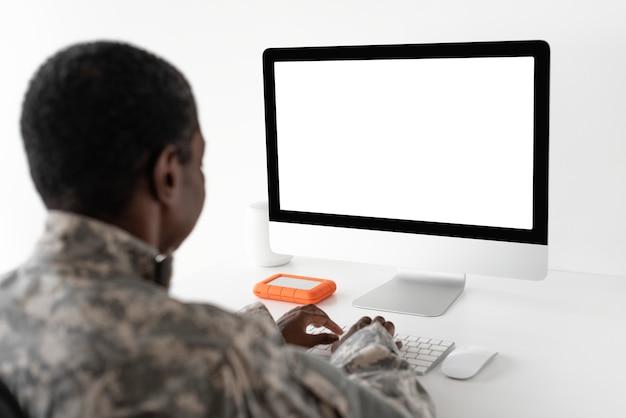 Oficial militar usando tecnologia de computador do exército