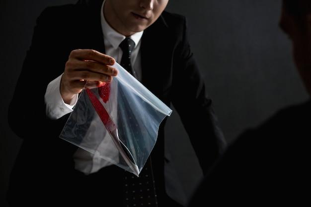 Oficial mostrando uma evidência em investigação criminal