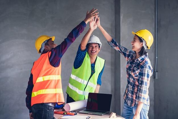 Oficial trabalho de equipe é feliz e se juntar as mãos para comemorar no sucesso do acabamento no trabalho