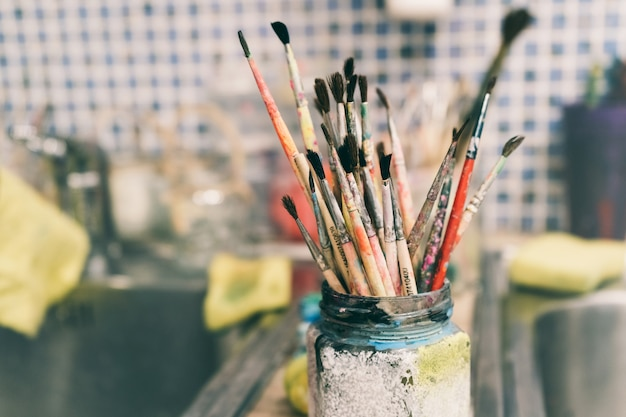 Oficina criativa do artista. pincéis de pintura em uma jarra. muitos pincéis para pintar em um só lugar