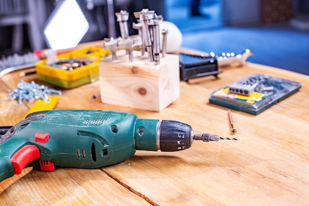 Oficina de carpintaria, broca e outras ferramentas mentem sobre a mesa close-up