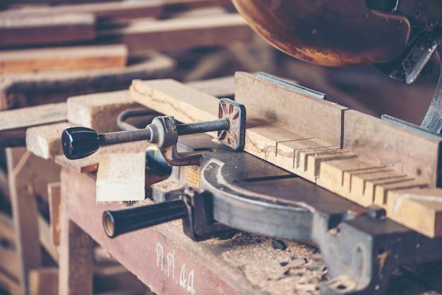 Oficina de carpintaria: mesa de trabalho de carpinteiros com diferentes ferramentas e corte de madeira