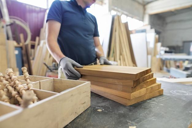 Oficina de carpintaria que fabrica móveis de madeira. detalhes de madeira nas mãos de carpinteiro