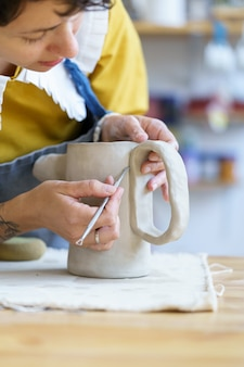 Oficina de cerâmica - processo de pequena empresa de modelagem e modelagem de jarra de argila em estúdio ou oficina de cerâmica