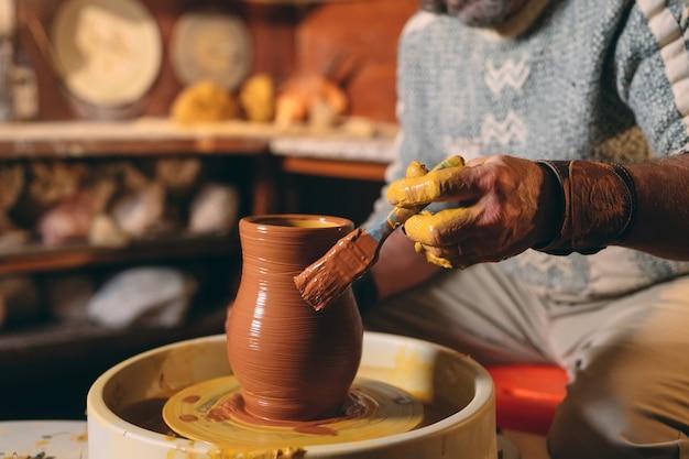 Oficina de cerâmica. um homem sênior faz um vaso de barro. modelagem em argila