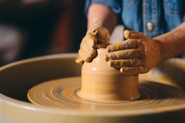 Oficina de cerâmica. uma garotinha faz um vaso de barro. modelagem em argila