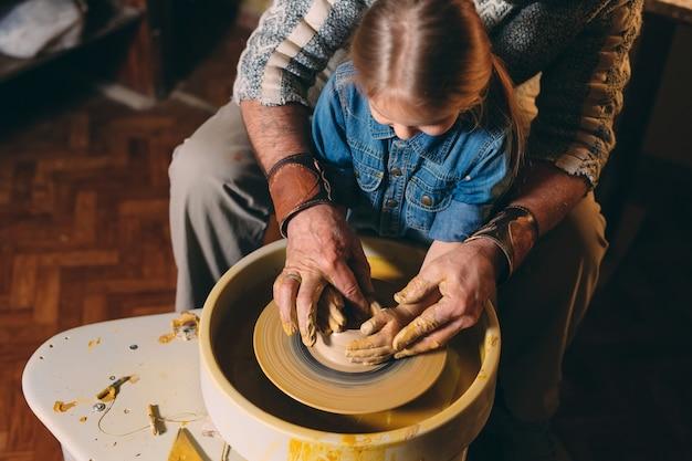Oficina de cerâmica. vovô ensina cerâmica para neta. modelagem em argila