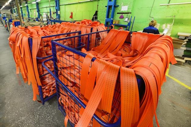 Oficina de costura para produção de tiras de nylon. recipiente de malha metálica com fitas de nylon para fazer lingas de carga macias.