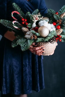 Oficina de floricultura. mulher de vestido azul segurando o pote com árvore do abeto, veado, bolas de natal, bastões de doces.