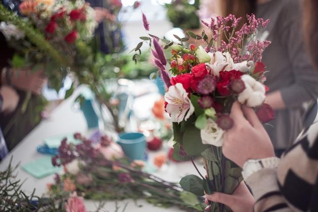 Oficina de florista, fazendo buquês e arranjos de flores. foco suave