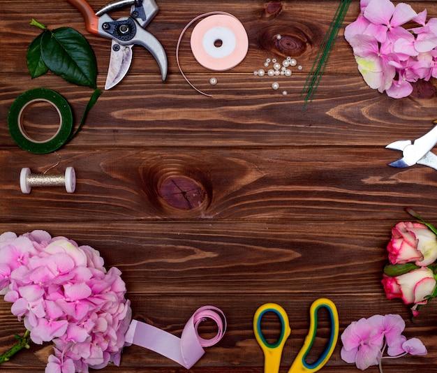 Oficina de floristas. ferramentas: tesoura, podador no fundo de uma mesa com flores. crie arranjos florais para o dia das mães ou o dia dos namorados