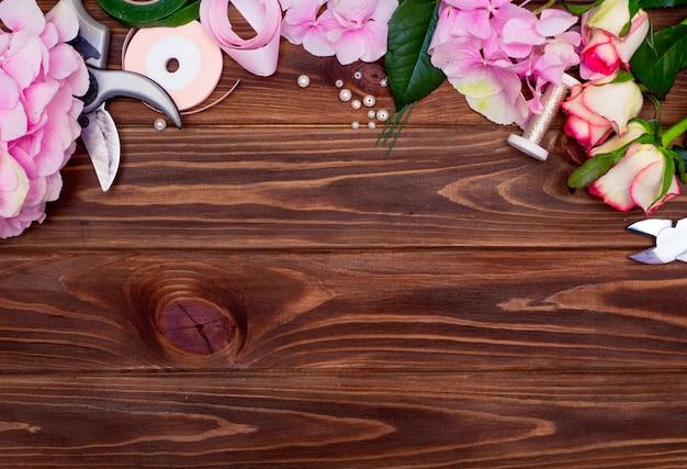 Oficina de floristas. ferramentas: tesoura, podador no fundo de uma mesa com flores. crie arranjos florais para o dia das mães ou o dia dos namorados Foto Premium