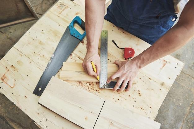 Oficina de marceneiro, um close de mãos com ferramentas.