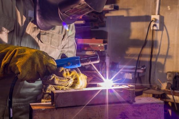 Oficina de soldador treinando um metal de solda com máscara protetora, uniforme e luva na fábrica