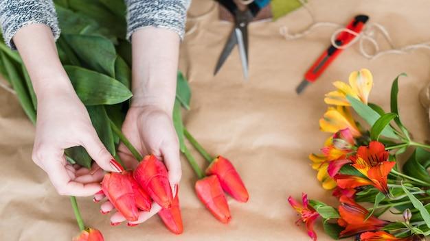 Oficina floral. mulher com as mãos fazendo um arranjo de flores de tulipas vermelhas. buquê de primavera