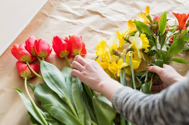 Oficina floral. mulher com as mãos fazendo um arranjo de flores de variedade de tulipas vermelhas, narciso amarelo e alstroemeria.