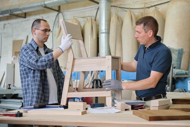 Oficina industrial de marceneiros, dois homens trabalhando com madeira, desenvolvendo móveis de design, cadeira estilosa de madeira sob encomenda