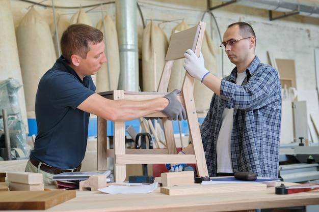 Oficina industrial de marceneiros, dois homens trabalhando com madeira