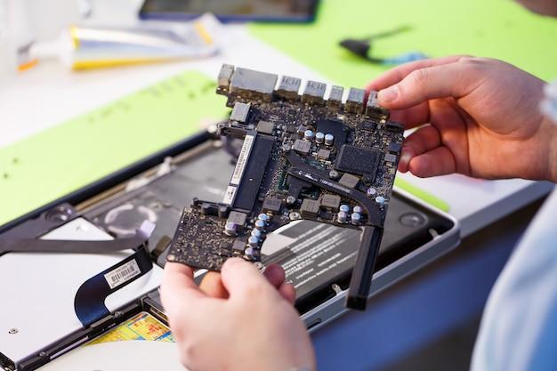 Oficina ou serviço profissional de conserto de computadores e tablets. perto de uma placa de computador. conceito de eletrônica. detalhe de um laptop em conserto