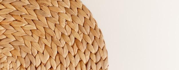 Ofício circular de fibras de rattan naturais marrons em fundo branco