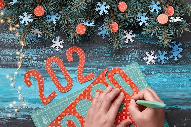Ofício de papel com número de corte de mão 2020, xícara de café e decorações de natal. vista plana, vista superior