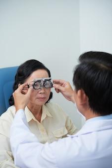 Oftalmologista ajudando paciente idoso