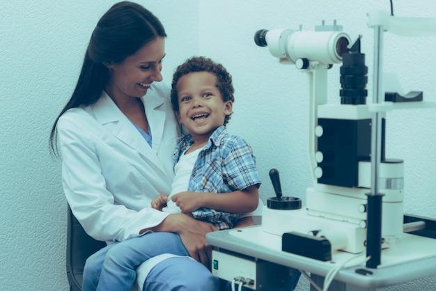 Oftalmologista está examinando os olhos do menino doente