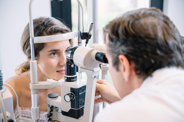 Oftalmologista examinando um paciente jovem