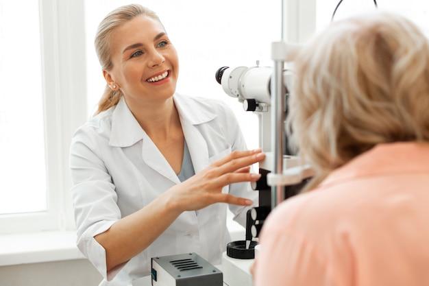 Oftalmologista sorridente positivo em uniforme branco trabalhando com paciente de cabelo curto