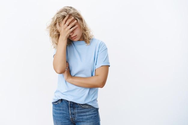 Oh deus, que humilhação. retrato de uma jovem cansada, esgotada e angustiada, fazendo facepalm, segurando a mão no rosto com decepção, posando infeliz sobre uma parede branca