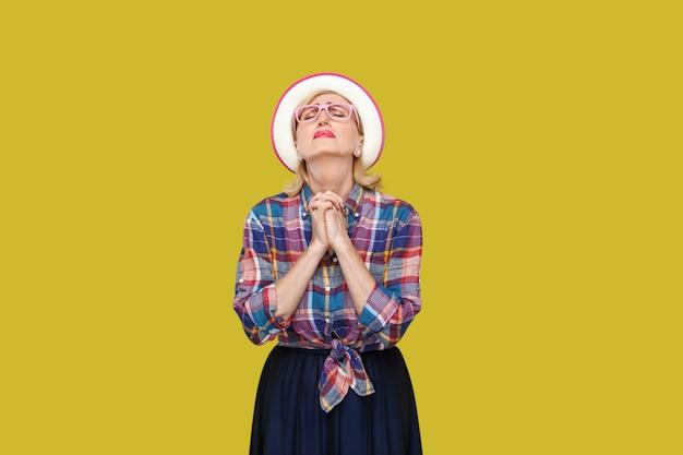 Oh meu deus por favor me ajude. retrato de mulher madura elegante moderna esperançosa em estilo casual com chapéu, óculos em pé com os olhos fechados e orando. estúdio interno tiro isolado em fundo amarelo.