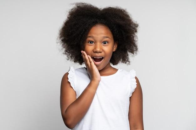 Oh meu deus, uau. retrato de uma menina pré-escolar espantada engraçada olhando para a câmera com expressão de espanto chocado e mantendo as mãos no rosto, gritando de surpresa. foto de estúdio isolada em fundo branco
