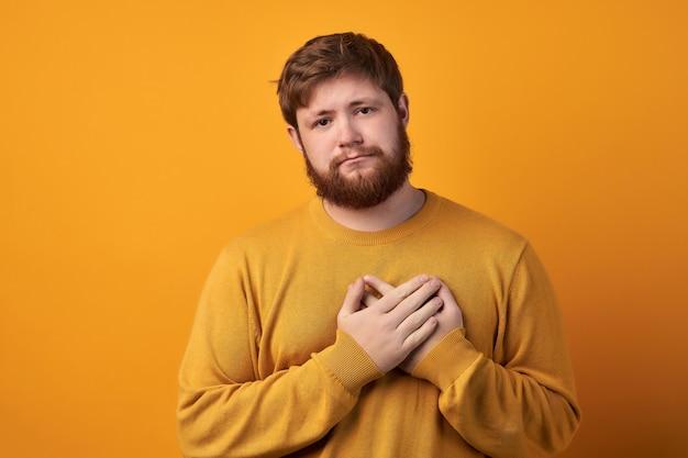 Oh, muito obrigado jovem atraente com a barba por fazer mantém as mãos no coração, expressa gratidão, fica de pé contra a parede branca do estúdio