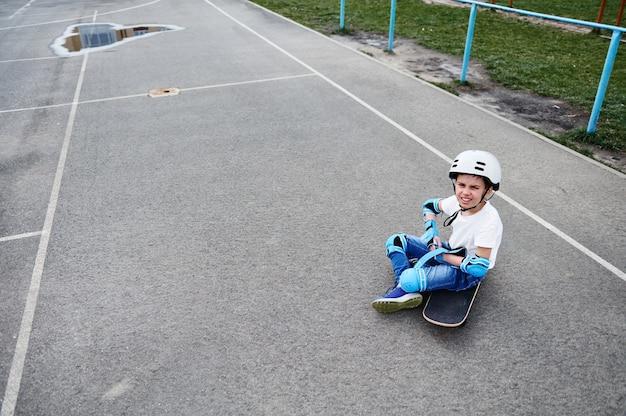 Oi sério em capacete de segurança senta-se no skate e se concentra em colocar equipamentos de proteção para o skatista
