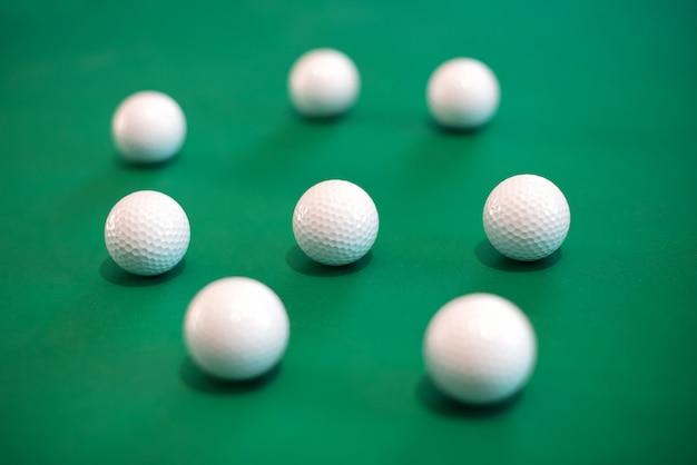 Oito bolas de golfe, deitado no tapete verde