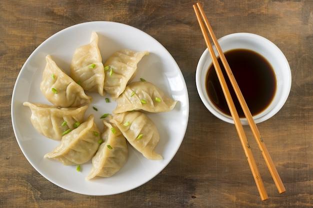 Oito jiaozi ou gedza cozido ou frito, servido com molho de soja.