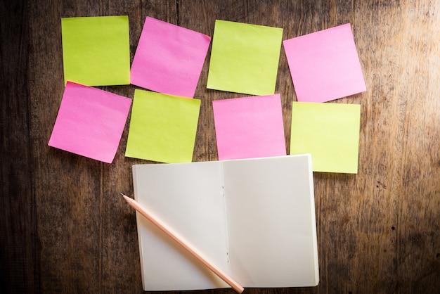 Oito notas em branco colorido e caderno e lápis