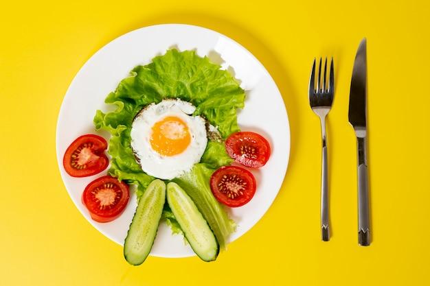 Oito ovos fritos leigos com prato de legumes frescos com talheres no fundo liso