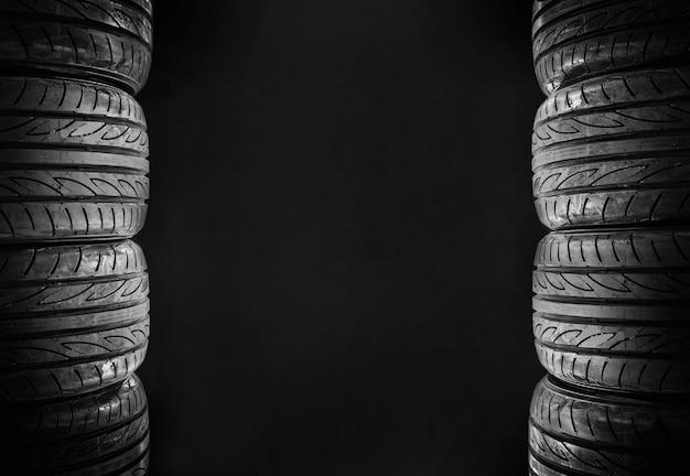 Oito pneus de carro isolados no espaço livre do fundo preto no meio para o texto.