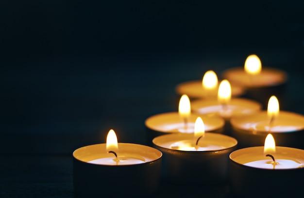 Oito velas acesas no escuro. foco seletivo