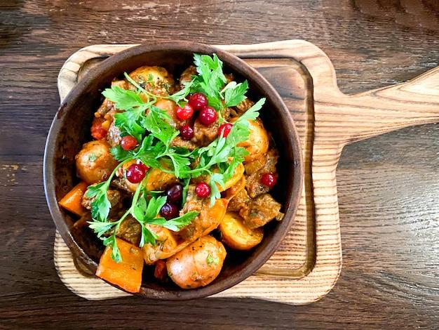 Ojahuri com vitela em um prato marrom é servido em um prato e fica em uma mesa de madeira
