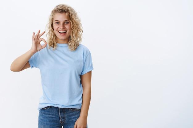 Ok, eu aprovo. retrato de uma jovem atraente de 25 anos, animada e satisfeita, com cabelos cacheados e olhos azuis, sorrindo alegremente e mostrando um sinal de ok como uma ideia incrível, recomendar o produto