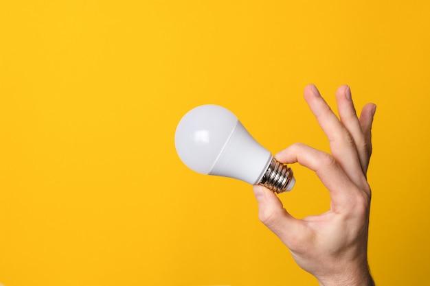 Ok gesto closeup mão segurando a lâmpada led branca contra uma bandeira amarela de fundo largo com copyspace. conceito de idéia, energia e ecologia