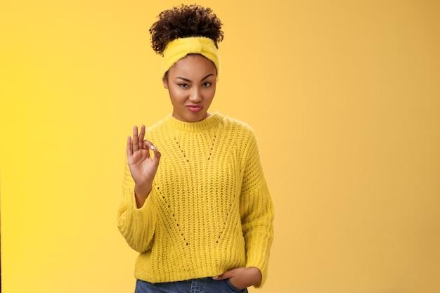 Ok, nada mal. retrato desonesto e sério confiante garota afro-americana mandona confira bom trabalho feito show ok gesto presunçoso aprovação concordar como bom trabalho, pé fundo amarelo satisfeito.