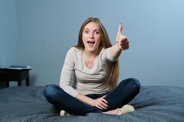 Ok sinal, jovem bonita sorridente bem-sucedida mostrando o polegar para cima, ok gesto de símbolo, sentada em casa na cama