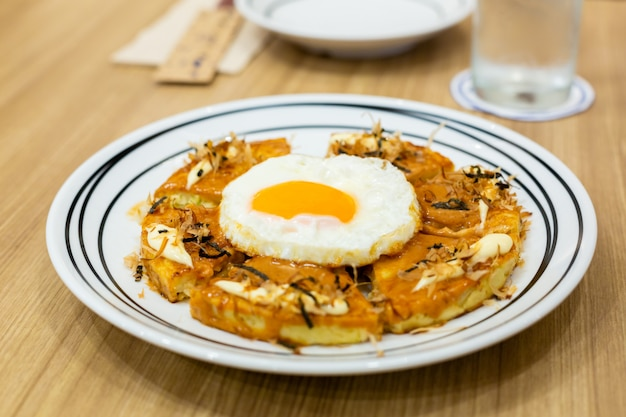 Okonomiyaki, pizza japonesa na mesa de madeira.