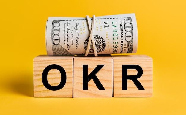Okr com dinheiro em um fundo amarelo. o conceito de negócios, finanças, crédito, renda, poupança, investimentos, câmbio, impostos